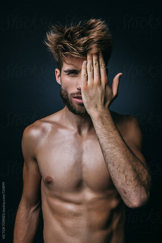 Muscular Shirtless Man in Dark Background Covering the Face with His Hand by VICTOR TORRES for Stocksy United
