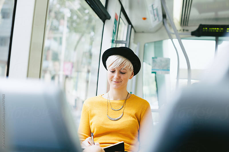 Modern and chic woman writing on her notebook sitting in the train. by BONNINSTUDIO for Stocksy United