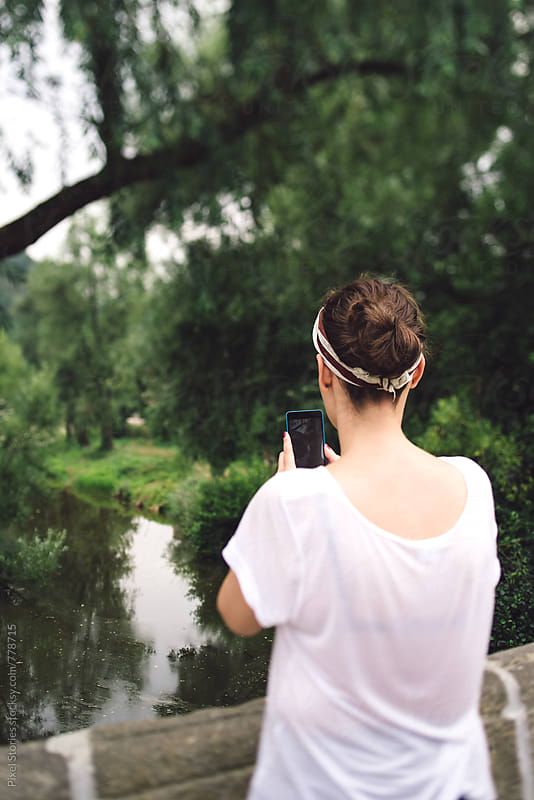 Young woman taking photos on bridge by Pixel Stories for Stocksy United