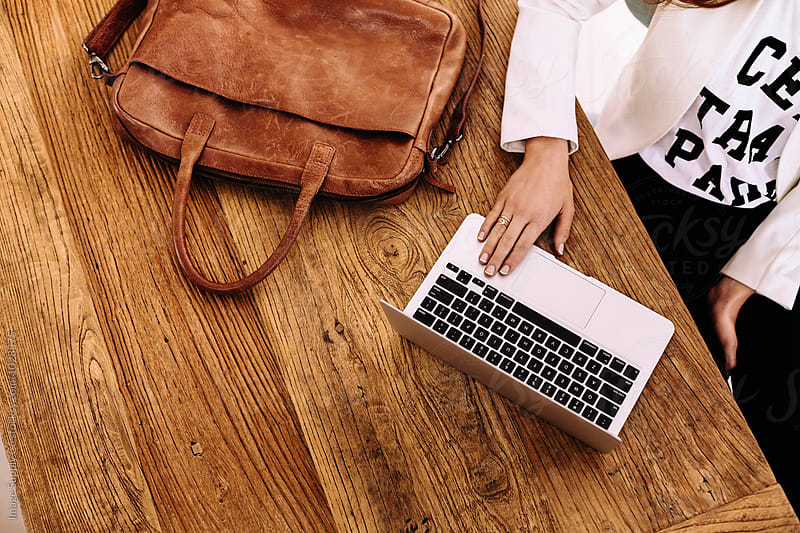 Young woman working on a laptop on wooden table  by Image Supply Co for Stocksy United