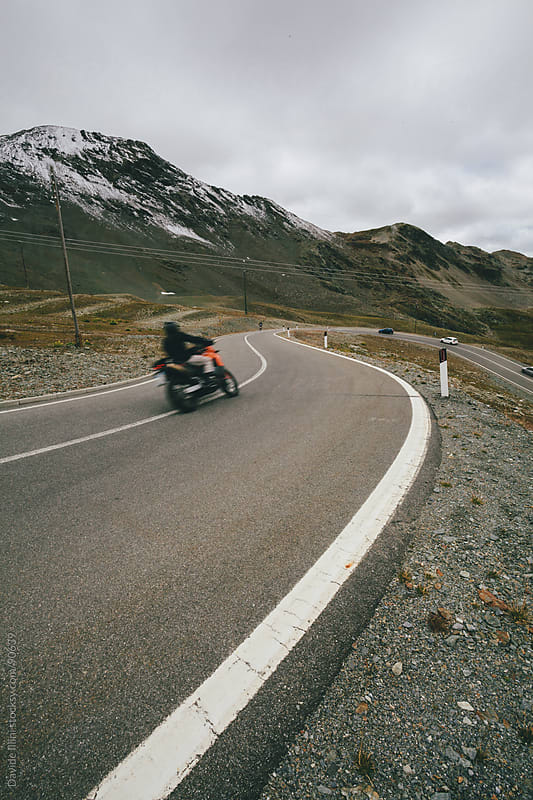 Biker on a mountain road by Davide Illini for Stocksy United