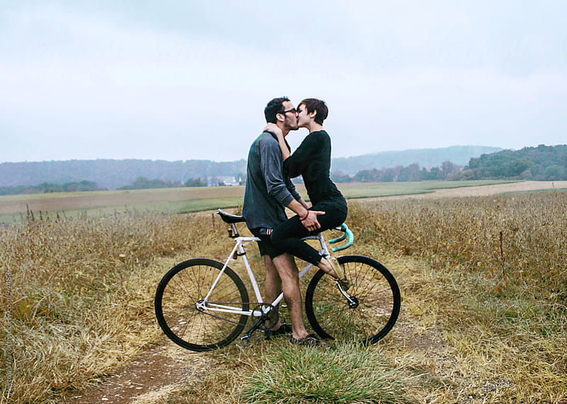 Man kissed woman in the rain as she sits on the handlebars of his bike by Peyton Weikert for Stocksy United