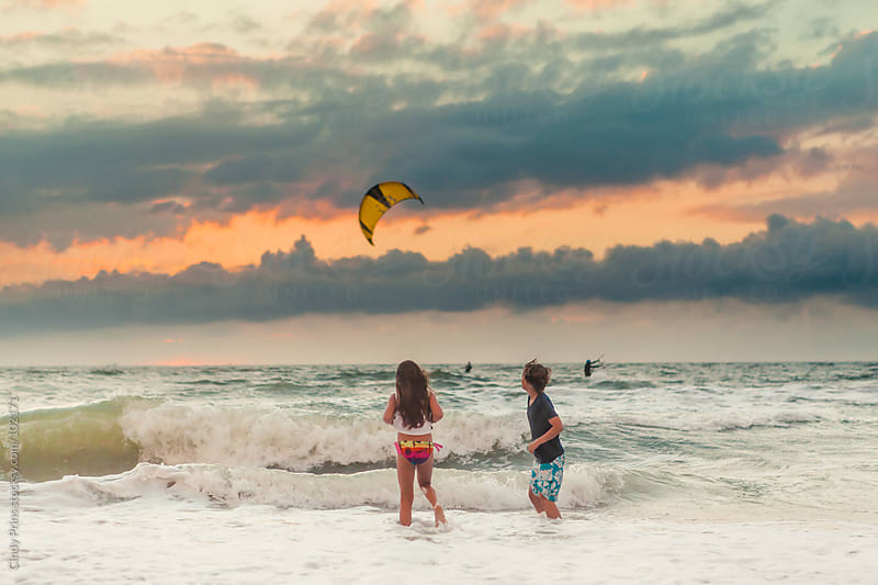 Kids standing in the ocean shore looking at a kitesurfer during sunset by Cindy Prins for Stocksy United