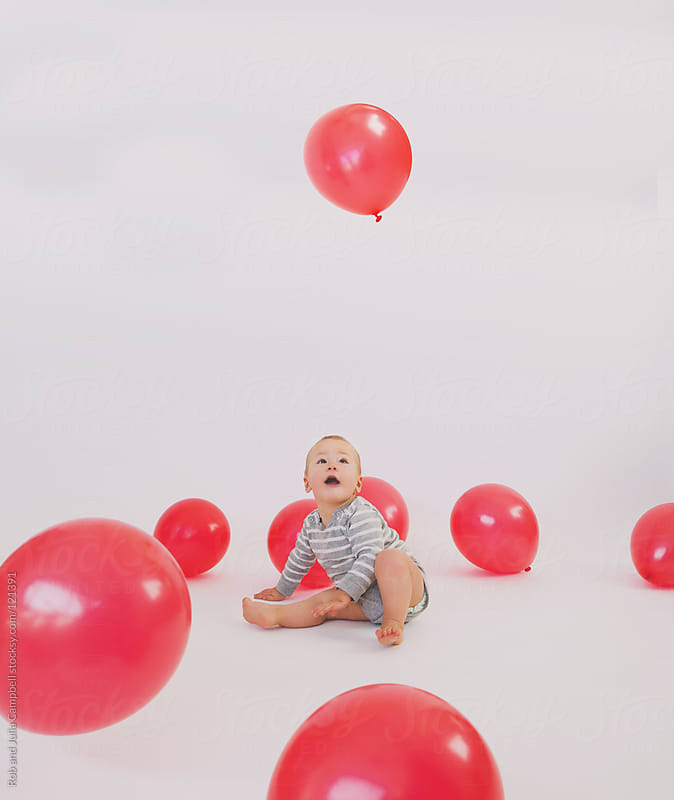 Baby boy stares up at red balloon on white studio background by Rob and Julia Campbell for Stocksy United