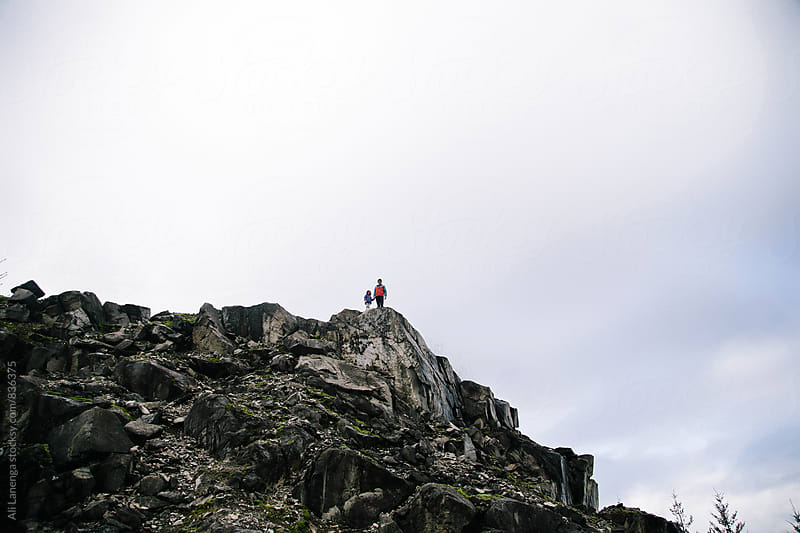 Father and daughter on rocky ledge by Ali Lanenga for Stocksy United