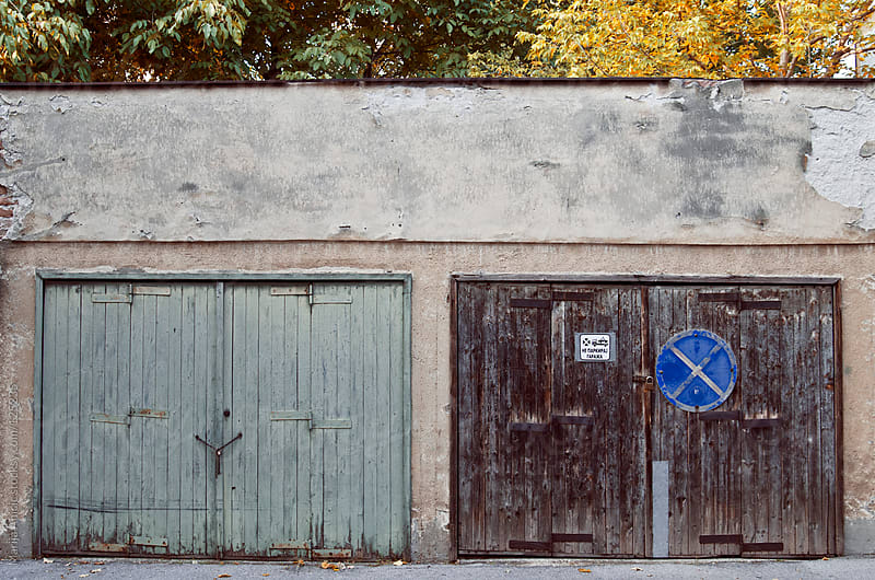 Two garage doors on the street with autumn trees behind by Marija Anicic for Stocksy United