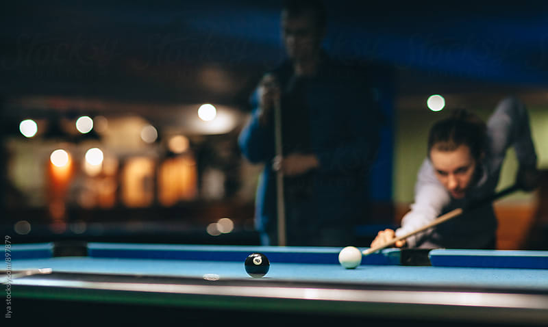Couple playing pool billiard game, young out of focus woman taking a shot. by Ilya for Stocksy United