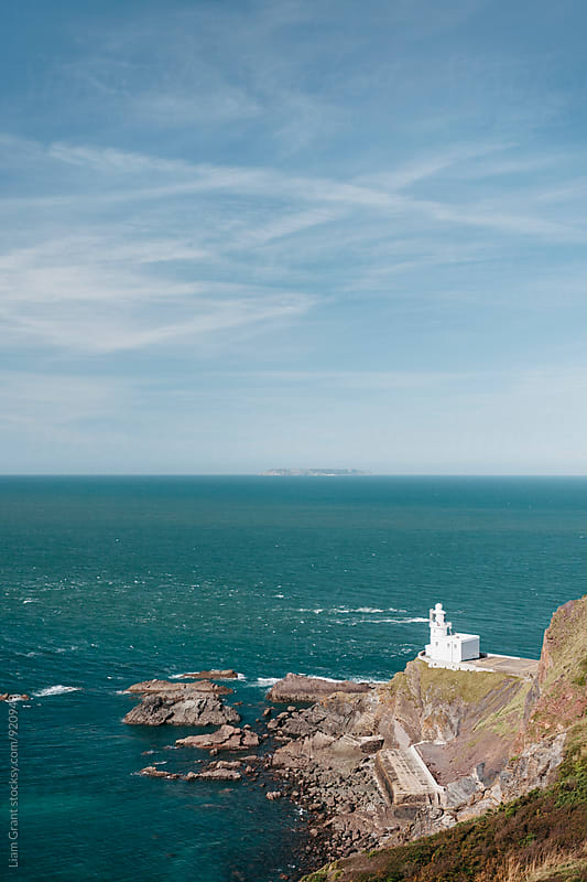 Lighthouse at Hartland Quay with Lundy Island beyond. Devon, UK. by Liam Grant for Stocksy United