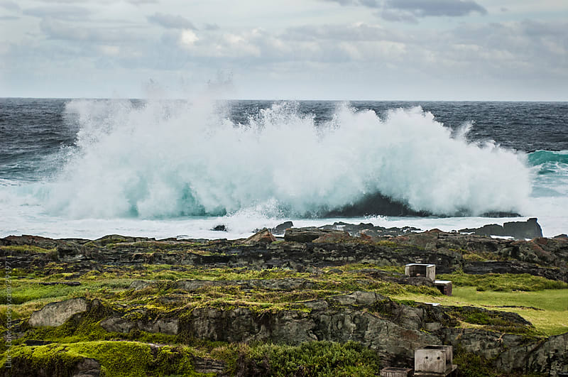 massive wave breaking on a rocky beach by Lior + Lone for Stocksy United