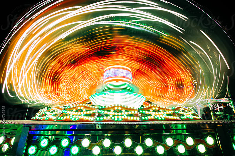 Spinning ride in a fair at night with colorful lights by Inuk Studio for Stocksy United