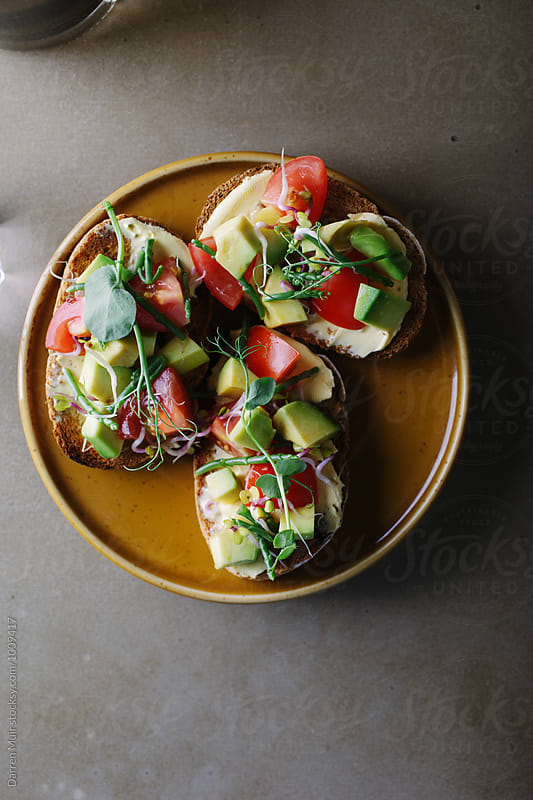 Avocado,tomato and samphire toasts on a plate.Healthy brunch. by Darren Muir for Stocksy United