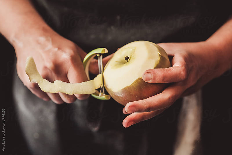 Hands peeling a apple by Vera Lair for Stocksy United