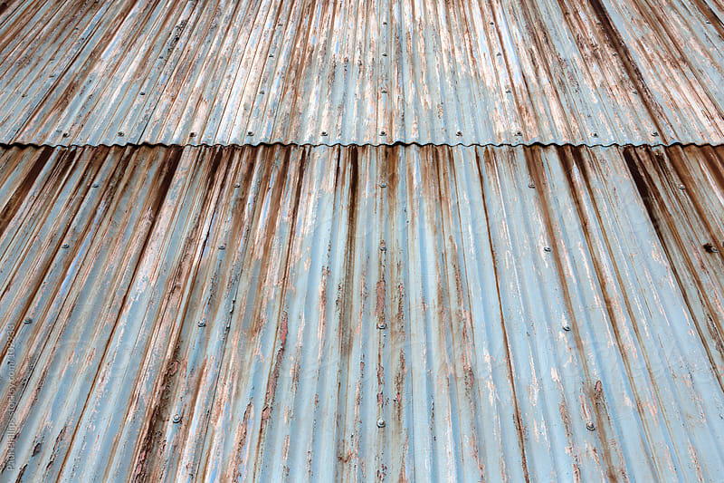 Old corrugated steel sheets on the outside of a building. Paint flaking and rust by Paul Phillips for Stocksy United