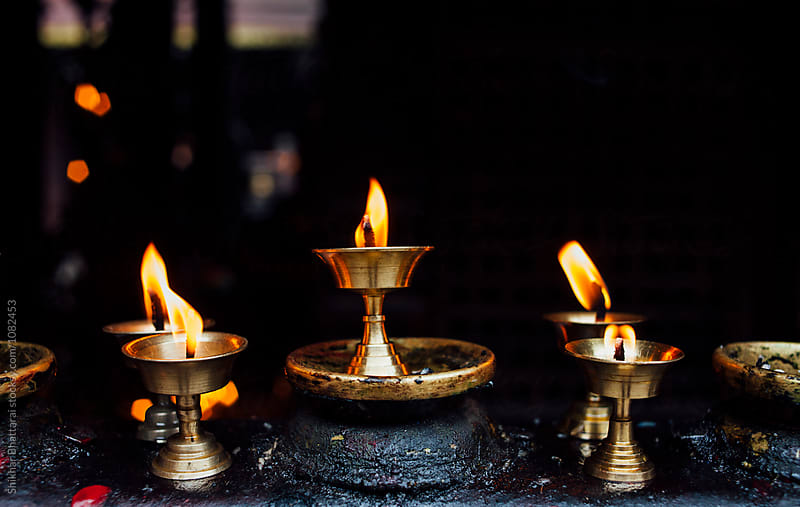 Close up of butter lamps in a temple in Kathmandu. by Shikhar Bhattarai for Stocksy United