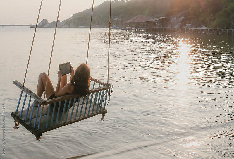 Woman relaxing using tablet computer in seated rope swing over the ocean water on tropical island by Soren Egeberg for Stocksy United