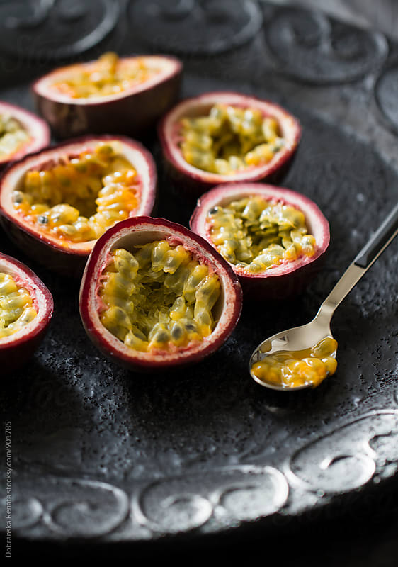 Halved passion fruits with spoon by Dobránska Renáta for Stocksy United