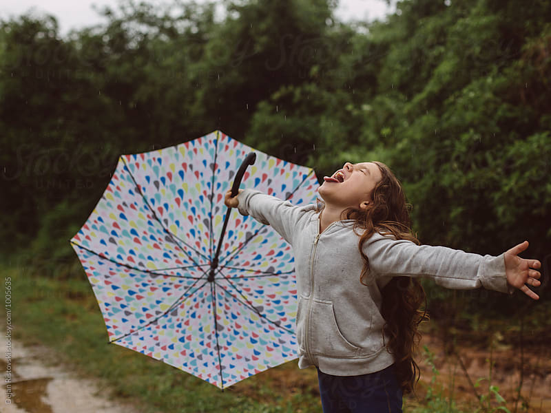 A child playing on a rainy day. by Dejan Ristovski for Stocksy United
