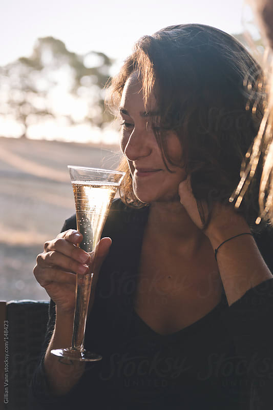 young woman with champagne by Gillian Vann for Stocksy United