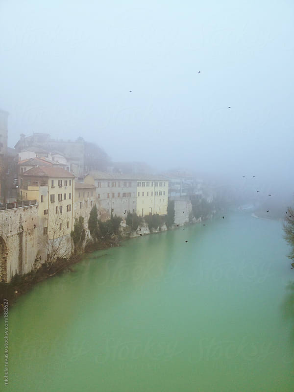 Group of typical houses overlooking a river surrounded by fog by michela ravasio for Stocksy United