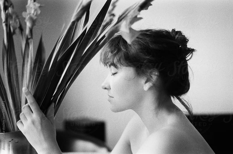 A black and white film portrait of young beautiful woman with flowers by Anna Malgina for Stocksy United