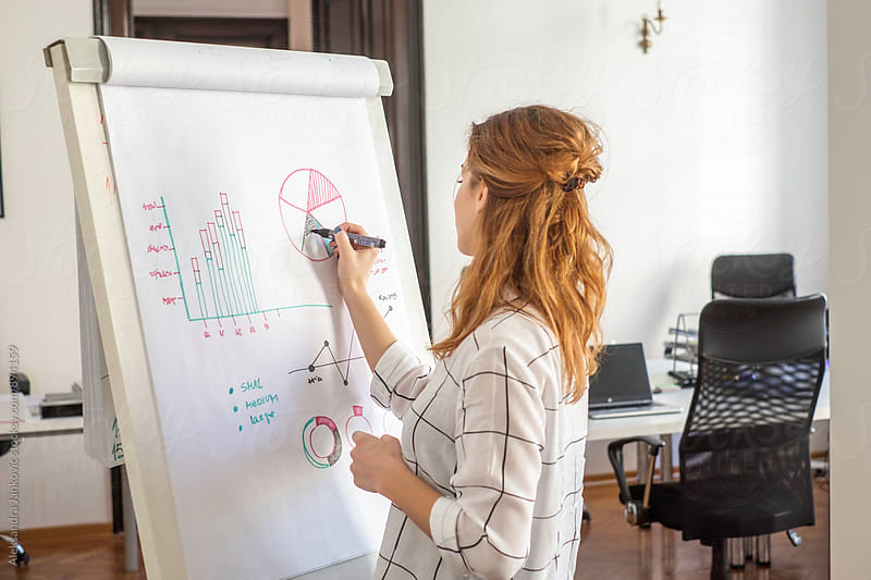 Woman Drawing Charts on the Board at the Business Meeting by Aleksandra Jankovic for Stocksy United