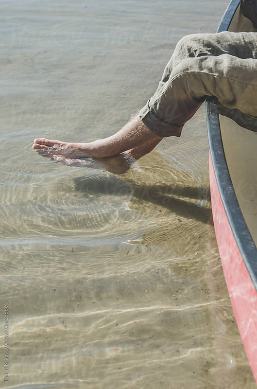 A Man's Feet in Water by Tomas Kraus for Stocksy United