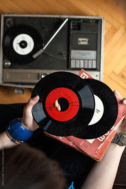 Girl is holding a few vinyl records above the portable turntable by Jelena Jojic Tomic for Stocksy United