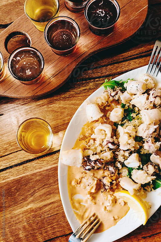 lunch in a brewery, salt and pepper fried squid, with a beer tasting paddle by Gillian Vann for Stocksy United