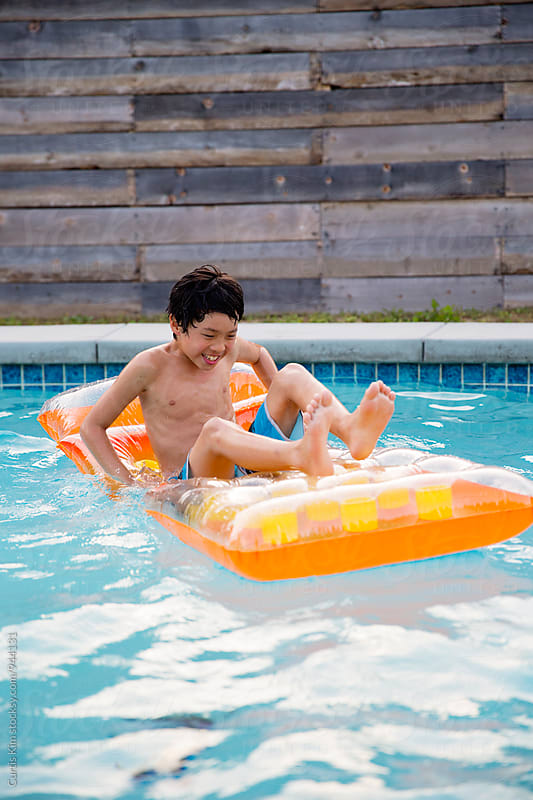 Young boy smiling and laughing in pool by Curtis Kim for Stocksy United