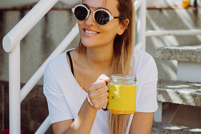Smiling young woman with sunglasses and cup in her hands by Susana Ramírez for Stocksy United