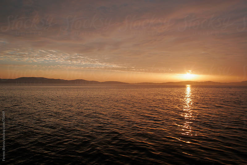 Sunset between the cloudsheet and the sea with twinkling golden  by Ferenc Boros for Stocksy United