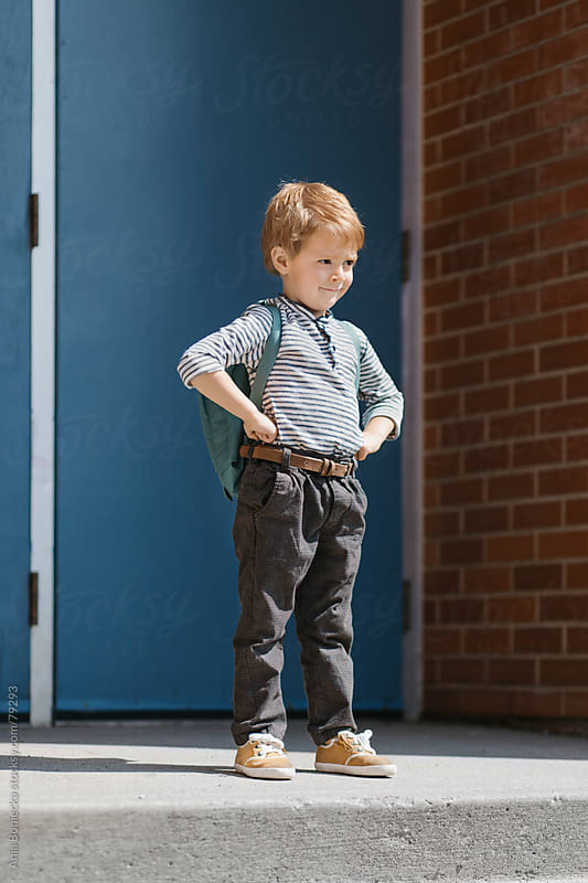 Boy standing upright with resolve in front of a school by Ania Boniecka for Stocksy United