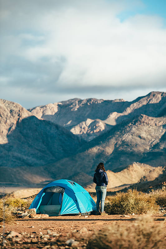 Hiker standing outside her tent looking at a rugged mountain landscape by Micky Wiswedel for Stocksy United