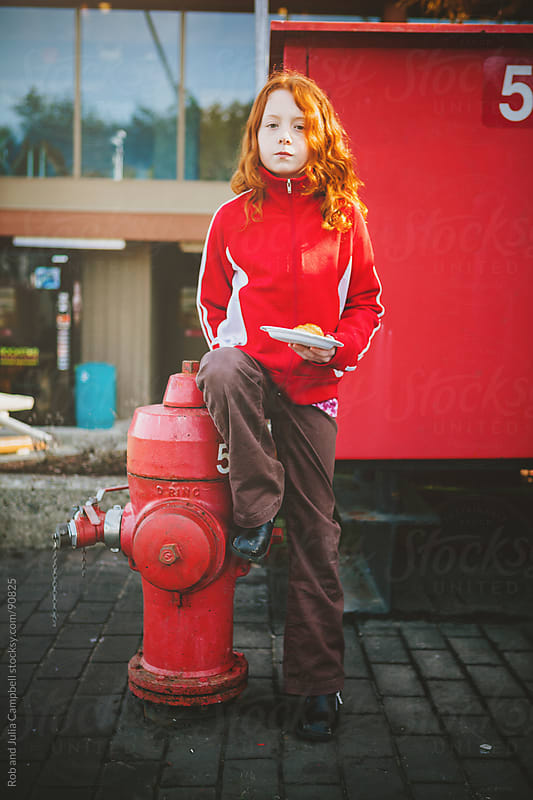 Redhead girl standing tough beside fire hydrant by Rob and Julia Campbell for Stocksy United