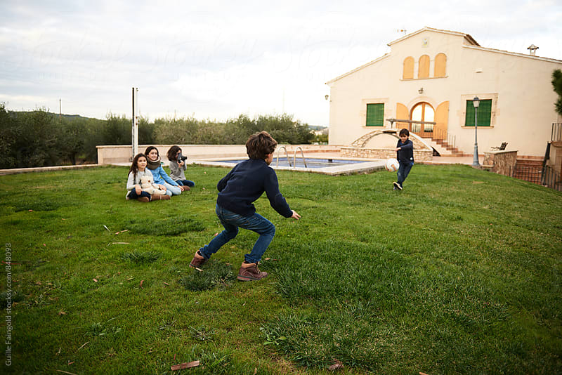 Children playing football on lawn by Guille Faingold for Stocksy United