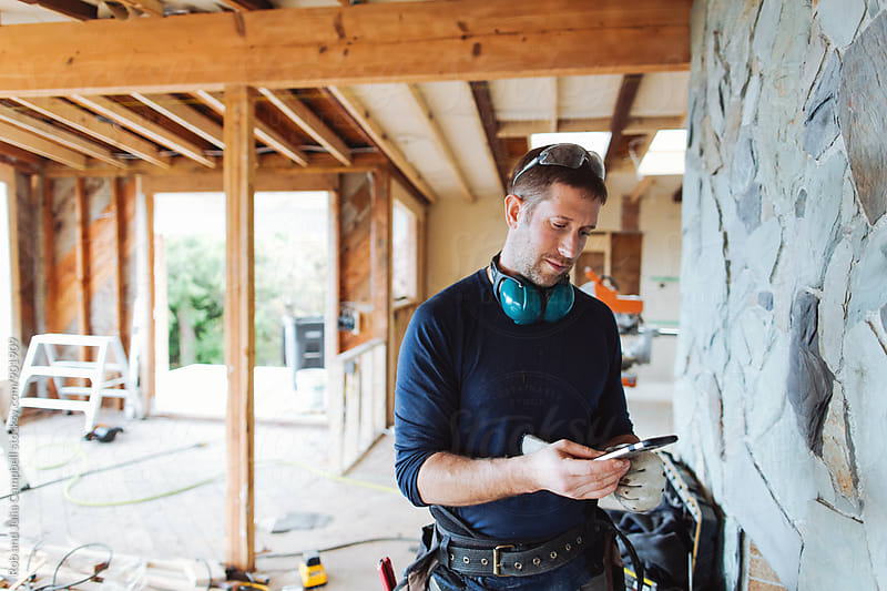 Carpenter contractor texting on cell phone inside home renovation by Rob and Julia Campbell for Stocksy United