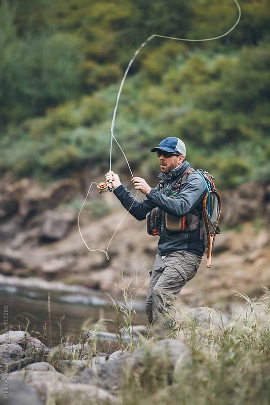 fly fisherman casting into a river by Micky Wiswedel for Stocksy United
