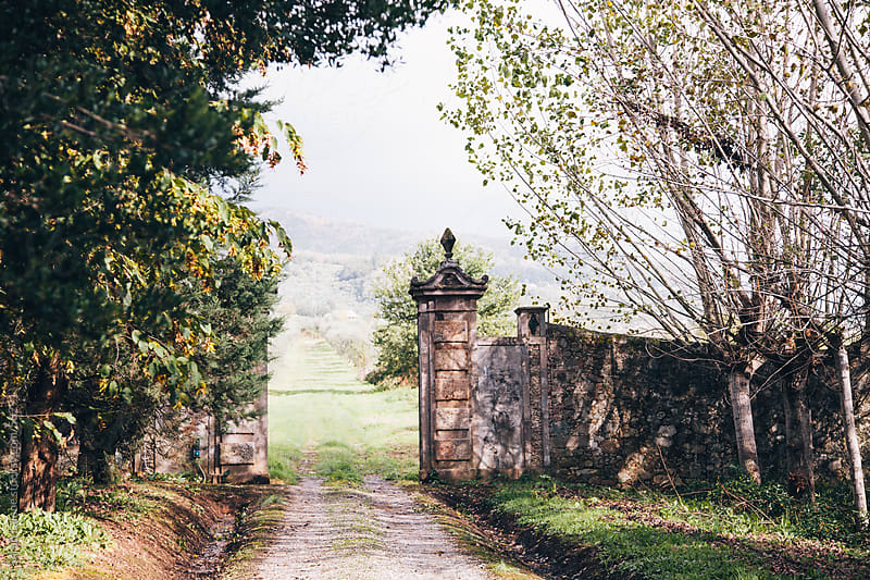 View through a stone gate into a valley in Tuscany by Sarah Lalone for Stocksy United