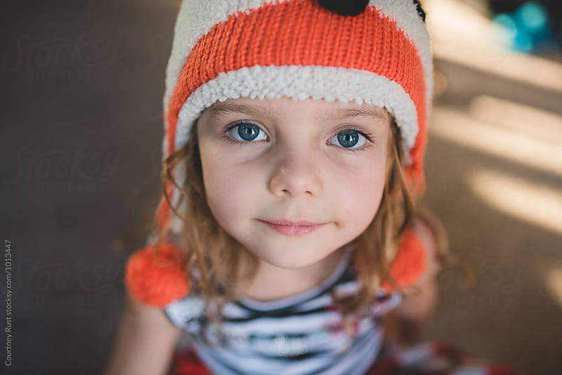 Little girl looking at camera with fox hat on  by Courtney Rust for Stocksy United