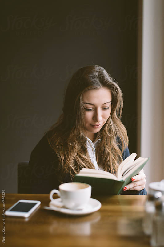 young woman sitting in a Coffee Shop and reading a book by Alexey Kuzma for Stocksy United