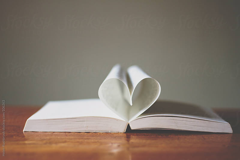 The pages of a book folded into a heart shape. by Helen Rushbrook for Stocksy United