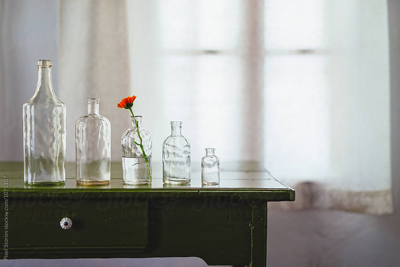 Glass bottles of decreasing size on table by Pixel Stories for Stocksy United