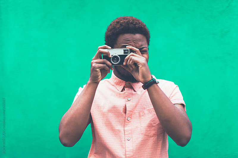Portrait of modern young black man taking photos with old camera in front green background. by BONNINSTUDIO for Stocksy United