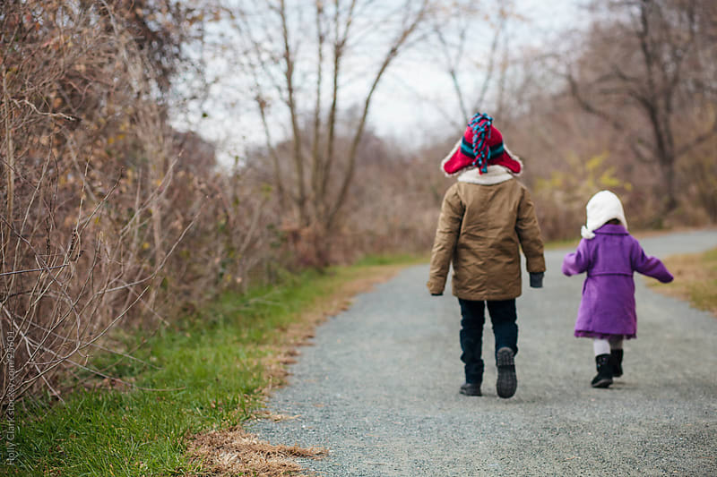 Two children walk down a path by Holly Clark for Stocksy United
