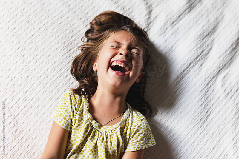 Young girl laying down laughing by Amanda Worrall for Stocksy United