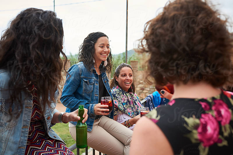 Cheerful friends with drinks having party in garden by Guille Faingold for Stocksy United