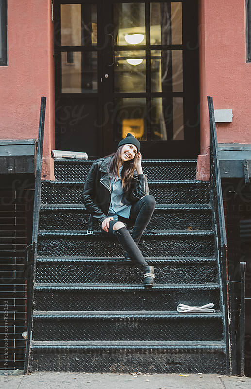 Young woman sitting on stoop in the city by Lauren Naefe for Stocksy United