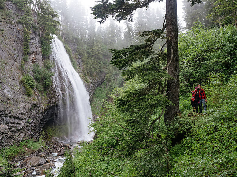 Young couple in flannel taking a selfie near gloomy waterfall in Washington by Jeremy Pawlowski for Stocksy United