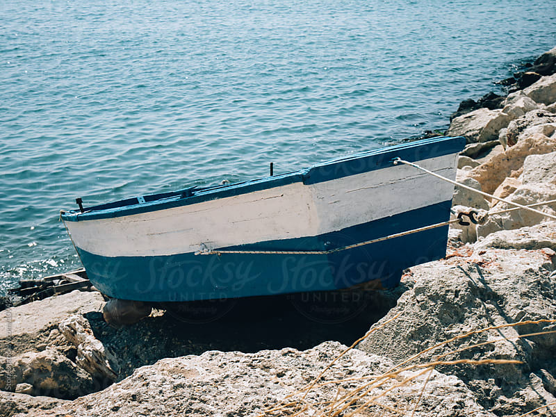 Old boat on rocky shore by Pixel Stories for Stocksy United