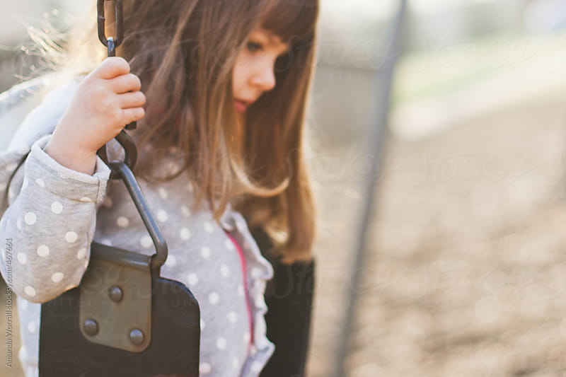 Close up of young girl on swing by Amanda Worrall for Stocksy United